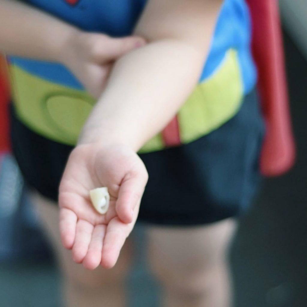 Barn som håller i en makaron, där en tablett är instoppad
