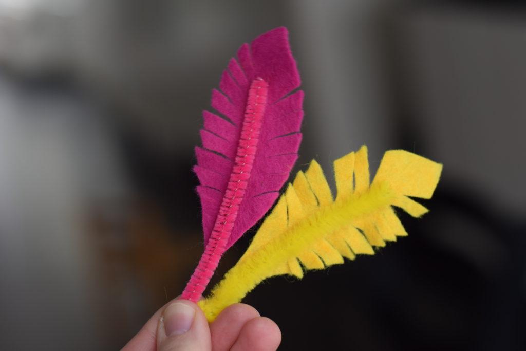 En rosa och en gul fjäder tillverkade av hobbyfilt och piprensare